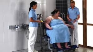 fat woman being helped in toileting by caregivers