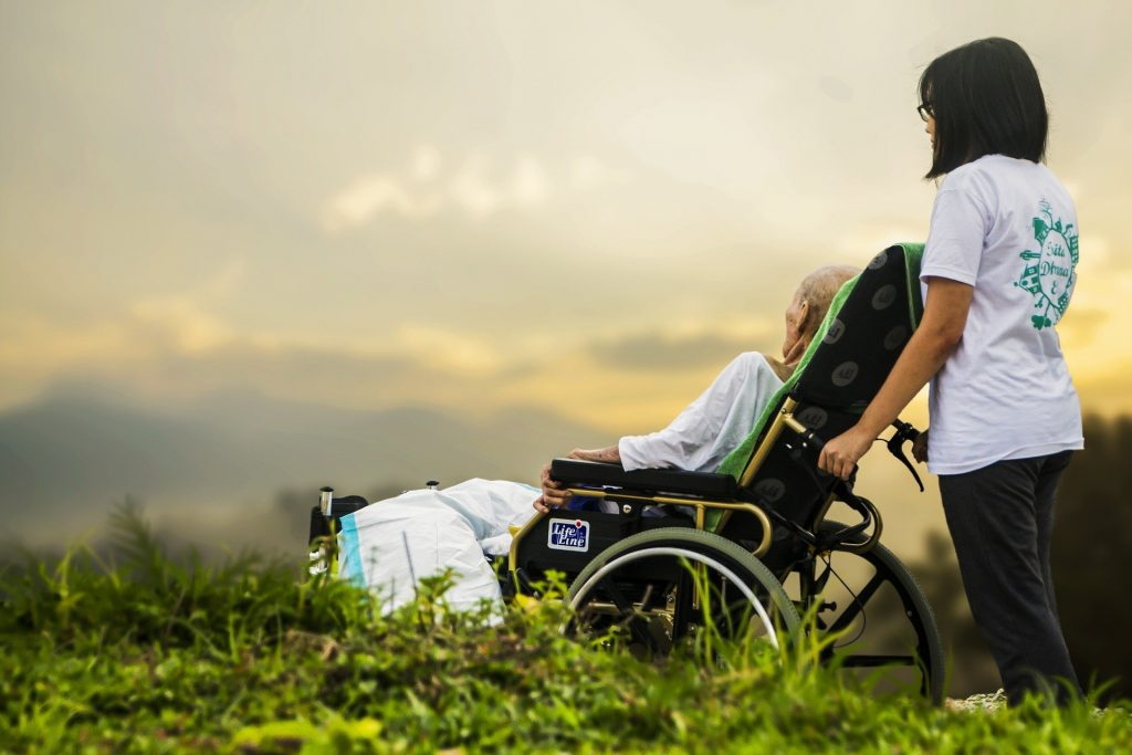 a hospice patient wheeled by caregiver